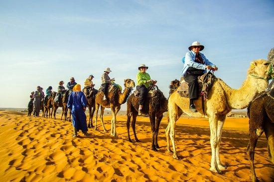 A line of camel riding tourists in Erg Chebbi