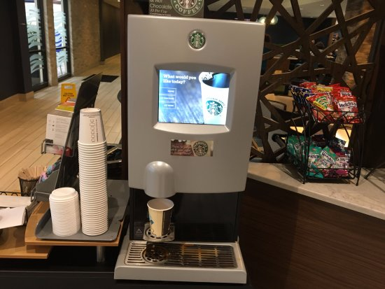Liverpool, NY: Maplewood Suites - Starbucks machine next to front desk