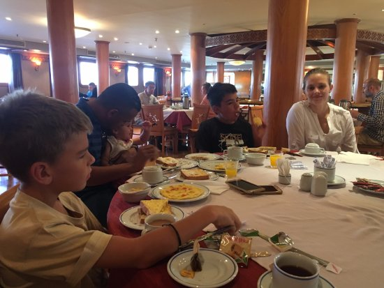 Habibitours - Day Tours : Breakfast on board the nile cruise, note our tour guide playing with our youngest daughter.