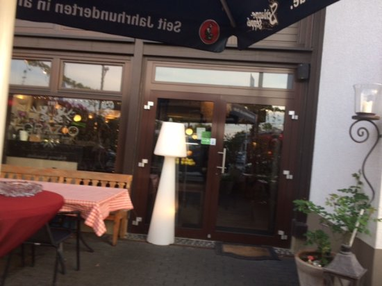 Ruesselsheim, Alemanha: Outside seating area and entrance to the restaurant