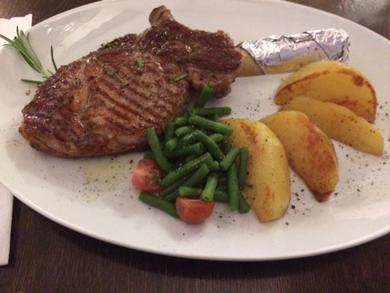 Ruesselsheim, Alemanha: Grilled veal chop with olive oil herb vinaigrette, rosemary potatoes and vegetables.