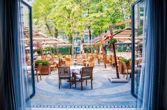 Athenee Palace Hilton Bucharest: A restaurant with a view over a peaceful terrace.