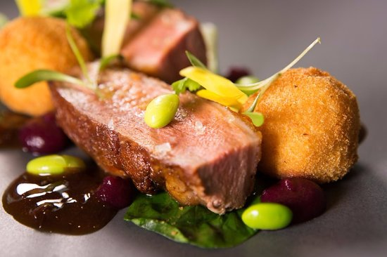 Whalley, UK: Roast breast of duck with wilted pak choi, leek and ginger purée, Edamme beans & wild rice aranc
