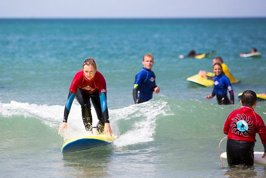 Perranporth, UK: Learner surfer applying the theory of standing up on her surfboard