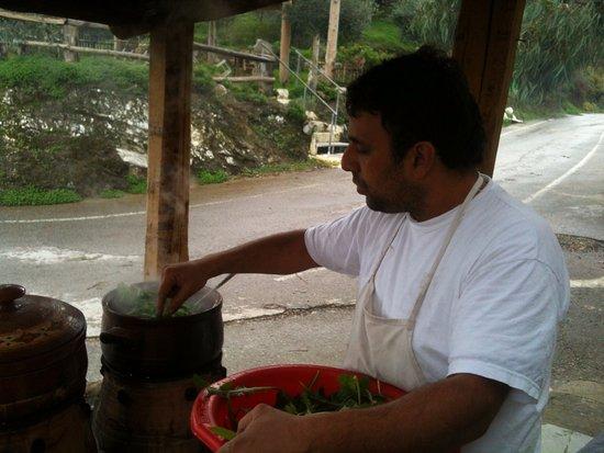 Ντουνιάς: the owner boils local greens over the open fire outside the taverna