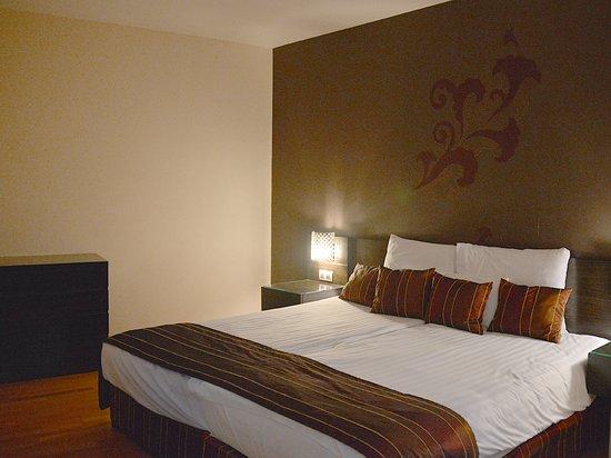 Hotel Regnum Residence: Sovrumsdelen i sviten med en byrå, sängbord och fåtölj (inte i bild)