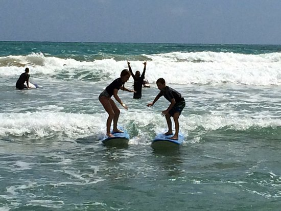 Luquillo Beach Boys Surfschool: Brother and sister riding waves together