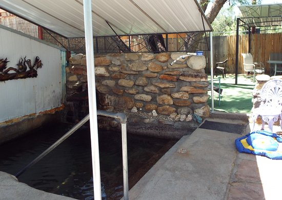 Safford, AZ: Communal tub with rock 'shower' in back corner and relax area under big tree in background