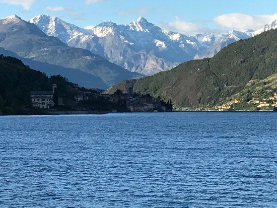 Сан-Сиро, Италия: La vista dai tavoli. Lago e montagne innevate in maggio. Unica.