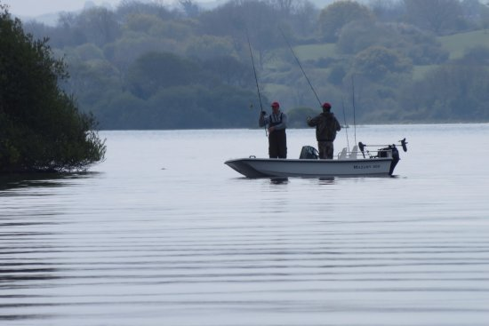Virginia, Irlanda: fishermen out on the lake, taken from the grounds