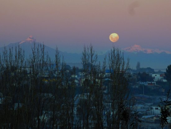 View of Volcano Corcovado at sunset with a full moon and Quellón if the foreground