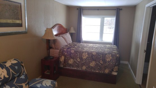 Malahat Bungalows Motel: Tall bed, sofa in front, bathroom to right, door behind photographer