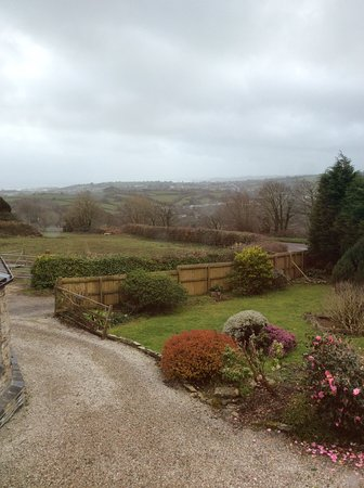 Par, UK: The garden and surrounding  countryside of the Roundhouse Mill.