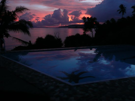 Villa Arjuna: sun set over the infinity pool and the ocean, in the distance the Nusa Penida Island.