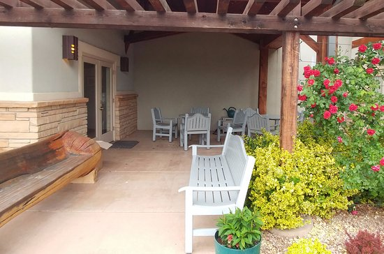 Palisade, CO: Patio with hand carved bench, tables and flowers
