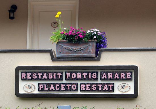 Tickle Pink Inn: Can you decipher the motto? Hint: it looks like Latin, but it's not.