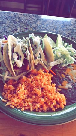 Victor, ID: Three yummy fish tacos garnished with avocado, tomatoes, sour cream, and cotija cheese.