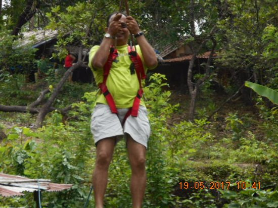 Sancordem, India: A senior member of the group also doing the zip line an activity within the premises.