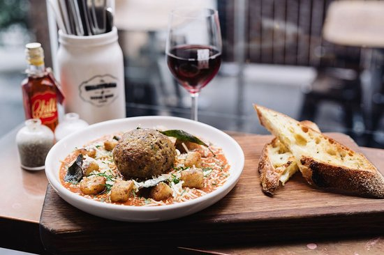 Windsor, Australia: Pan fried gnocchi, a giant pork meatball, creamy tomato sugo, and a glass of red. Perfection.