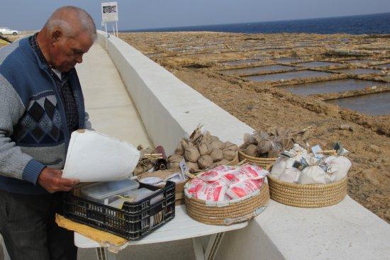 Zebbug, Malta: vendor sells bag of sea salt at salt pans