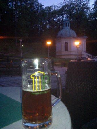 Rychnov nad Kneznou, Tsjekkia: ZWidok z tarasu hotelu na zabytkową kaplicę i lokalne piwo Kasztan.