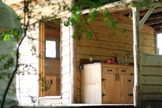 Bromyard, UK: The Yurts bathroom and kitchen, all powered by solar panels, are tucked in the tree line.