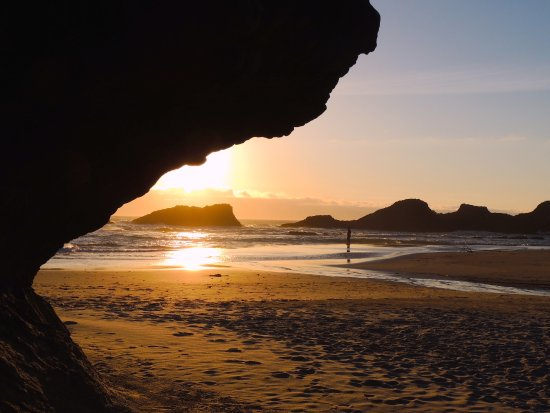 Seal Rock, OR: Sculpted by wind and water, a sandstone ledge obscures the sunset at the far end of the beach.