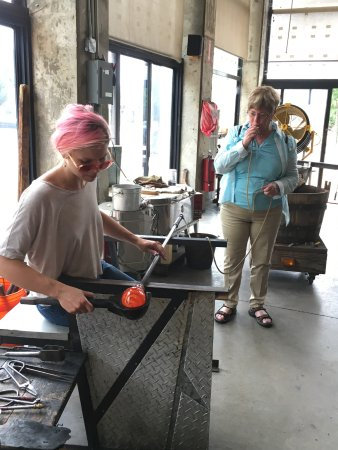 Flame Run Glass Studio and Gallery : Blowing molten glass into a wine glass.