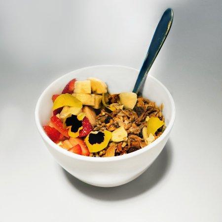 Buckhurst Hill, UK: Yoghurt and granola with strawberries and banana, and edible petals