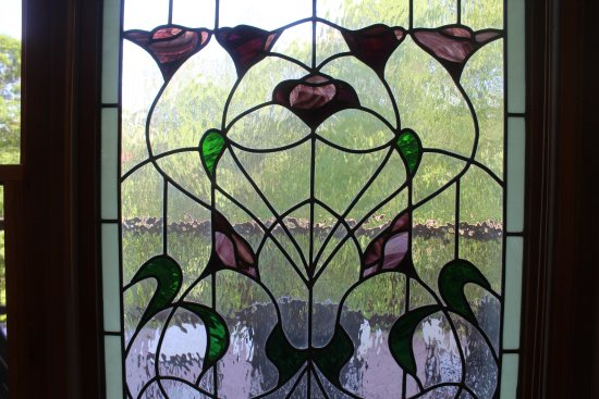 Arden, Βόρεια Καρολίνα: Stained glass window in dining area overlooks deck and wooded area & walking paths.