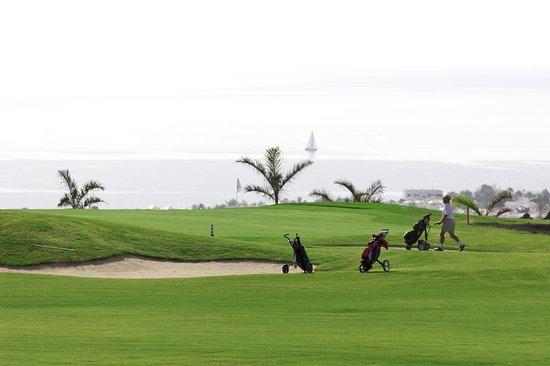 Lanzarote Golf Resort: Green Hole 17, Puerto del Carmen, a sailing boat and the Atlantic ocean