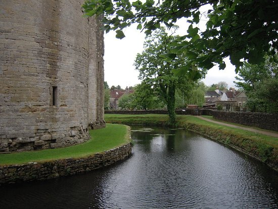 Nunney, UK: Castle's water moat and pathway to castle