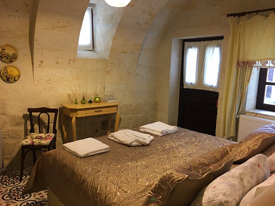 Mustafapasa, Turquía: Mağara ve taş yapının gizemli atmosferine teras manzarası ile eşlik eden özel bir oda.