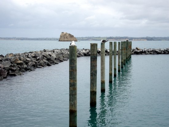 Whangaparaoa, New Zealand: Sea Wall and launch area, Frenchman's Cap Rock in background