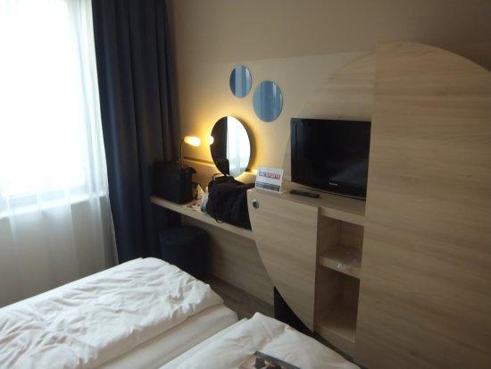 H2 Hotel Berlin Alexanderplatz: Blick vom Kopfende der Betten auf TV und Schreibtisch