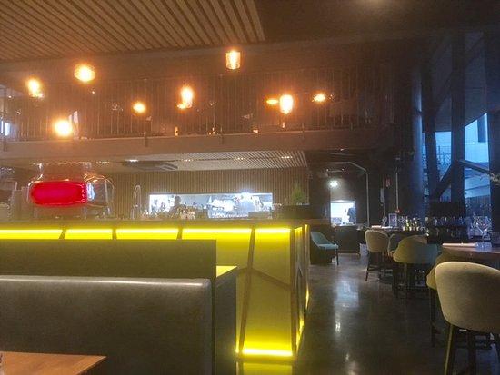la salle avec le bar central et la cuisine ouverte au fond