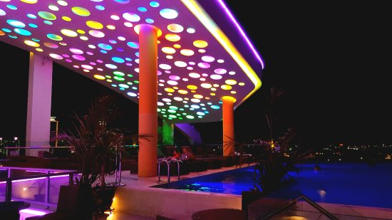 Infinity rooftop pool at night with lights