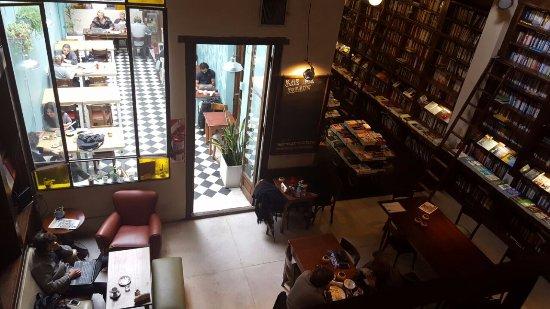 Libros del Pasaje Bar: patio con luz natural y livings adentro rodeado de libros