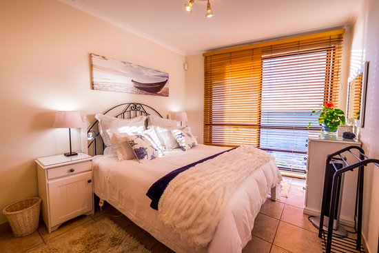 Gordon's Bay, South Africa: Romantic Beachside Cottage bedroom looks down onto waves lapping