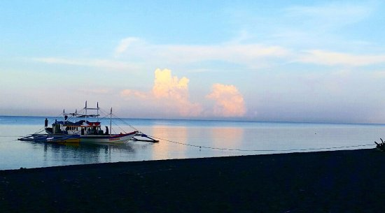 Sikatuna Beach Hotel: View in front of resort at 6am. Traditional Filipino banca boat on South China Sea.