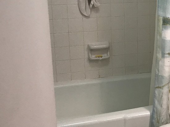 Coconut Beach Resort: Dirty tiles and tub. Ring around inside of tub from sunscreens and oil maybe?