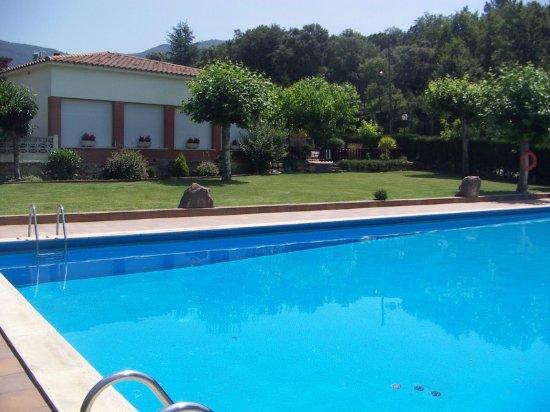 Sant Marti de Llemena, Spain: vista de la piscina y el restaurante al fondo