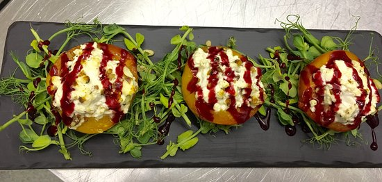 Vegetarian Baked Nectarine stuffed with Feta Cheese and Toasted Pinenuts on a bed of Pea Shoots