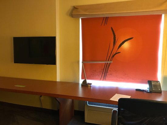 Instead of drapes, they used this beautiful shade with a full desk & tv on outside wall