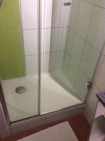 Ibis Styles Clermont Ferrand Le Brezet Aeroport : la douche on voit la porte et l'espace pour rentrer