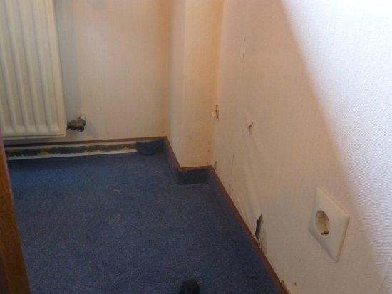 Gasthaus Hergenhahn: Beschädigte Tapete und abgefallene Teppichleiste unter dem Fenster.