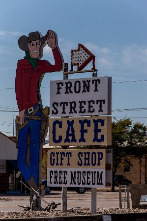 Ogallala, NE: Sign of cowboy at entrance parking lot Front street