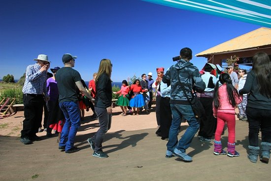 All Ways Travel: Tourists dancing with local people begore lunch (trout and....chips)