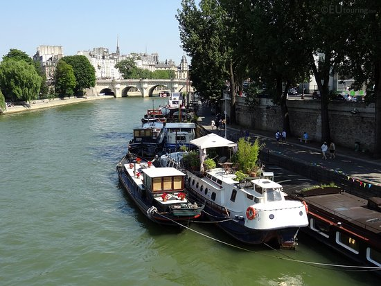 Pont-Neuf: Multiple houseboats moored up along the River Seine, leading towards the oldest bridge in Paris