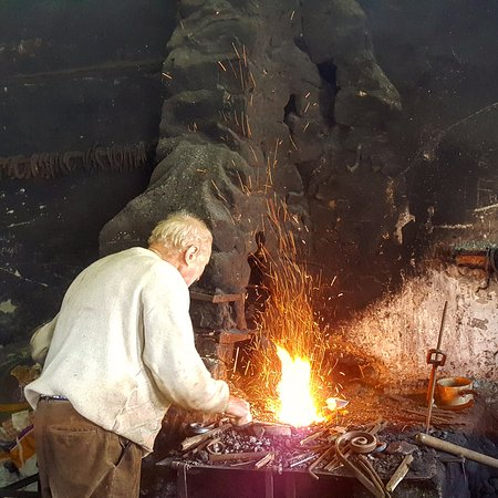 Boolteens, Ireland: 4th Generation Blacksmith Florence in his forge opposite The Anvil Bar